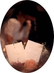 invitation in foreground, couple kissing in background